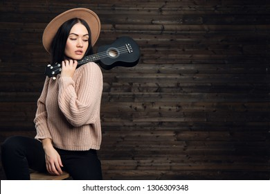 Young brunette women play ukulele guitar in studio on wooden background.
