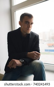 young brutal guy brunette posing near the window of the old building. office style clothes: jeans and a black shirt. emotional portrait. short hair and clean skin