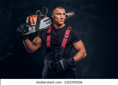Young brutal logger posing with a chainsaw on his shoulder and looks sideways