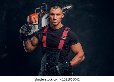 Young brutal logger posing with a chainsaw on his shoulder and looking at a camera with a confident look
