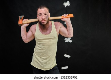 Young brutal man with a beard, bodybuilder in a yellow shirt standing, posing against a black background with patches with an ax. Beautiful male body. Concept art. Model right in front of the camera.