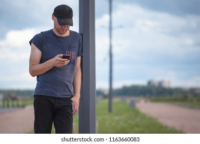 young brutal man with a bristle stands with a smartphone in the open air
