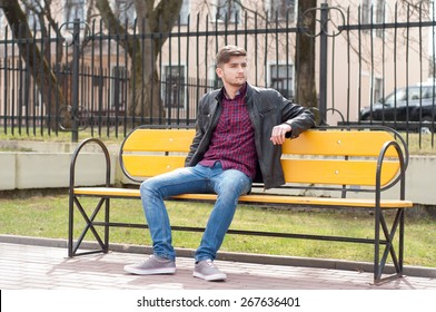 Young brutal man sitting on the bench