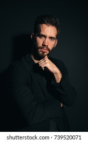 young brutal man with a thick beard on the face posing in Studio. strong healthy teeth and clean skin. emotional portrait. business style in clothes: wearing a black t-shirt and jacket