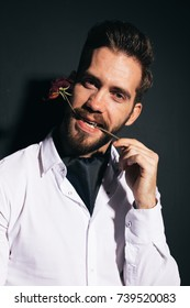 young brutal man with a thick beard on the face posing in Studio. strong healthy teeth and clean skin. use the pressed plant: the rose. emotional portrait. dressed in a white shirt with a light scarf