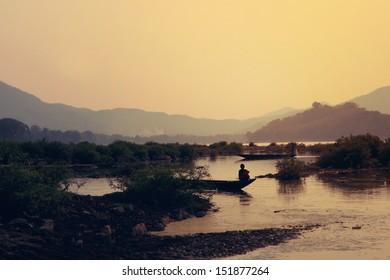 young buddhist monk on fisher boat at sunset on Mekhong in Luang Prabang - Laos