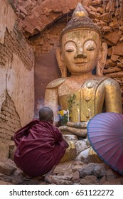 Young buddhist monk praying in front of Buddha statue inside ancient ruined pagoda in Indein, Myanmar