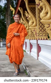 Young Buddhist Monk Walking And Smiling To The Camera