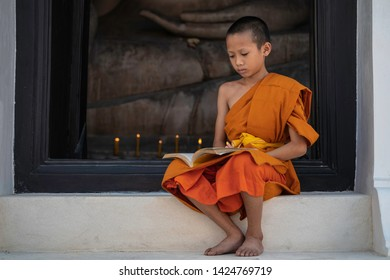 Young Buddhist novice monk reading, Young Buddhist novice monk study inside monastery. Asian young Buddhist monk In one of the temple in Thailand.