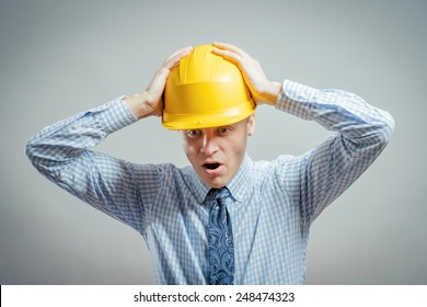 Young builder in helmet disappointed