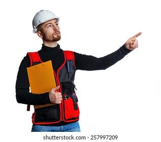 Young builder holding a folder and points a finger at something, isolated on a white background