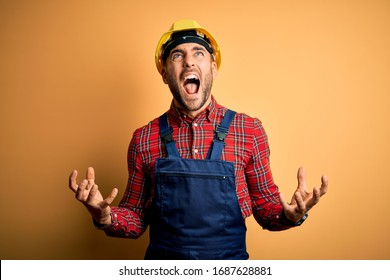 Young builder man wearing construction uniform and safety helmet over yellow isolated background crazy and mad shouting and yelling with aggressive expression and arms raised. Frustration concept.
