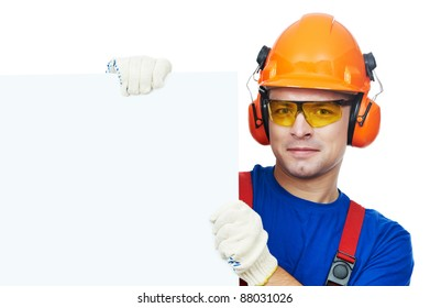 Young builder in safety equipment goggles hard hat earmuffs isolated with white empty billboard