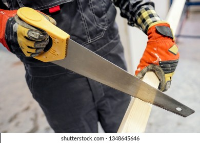 A young builder is sawing a wooden board with a hand saw. The concept of construction.