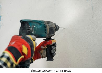 A young builder in a yellow helmet with a perforator, drills the wall in the room for repair. The concept of construction and repair.