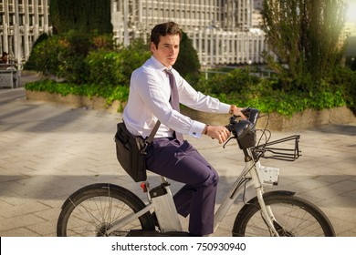 Young buinessman riding a bicycle to work in the city.