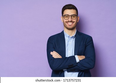 Young buisnessman wearing eyeglasses, jacket and shirt, holding arms crossed, looking at camera with happy confident smile, standing against purple background