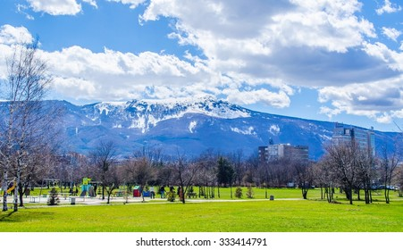 young bulgarians are walking through park in student city in sofia with vitosha mountain on background.