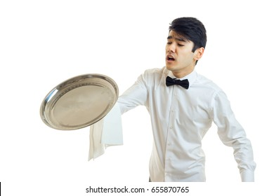 a young bumbling waiter drops on the floor of the empty tray is