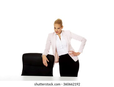 Young busiess woman standing behind the desk leanig on armchair