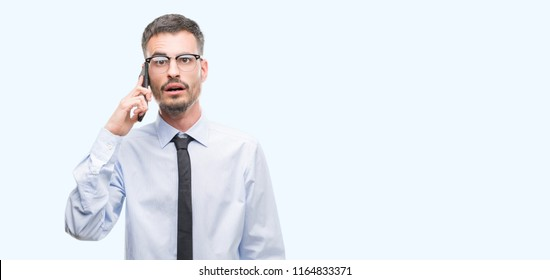 Young business adult man talking on the phone scared in shock with a surprise face, afraid and excited with fear expression