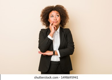 Young business african american woman looking sideways with doubtful and skeptical expression.