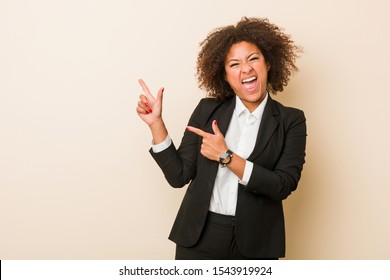 Young business african american woman pointing with forefingers to a copy space, expressing excitement and desire.