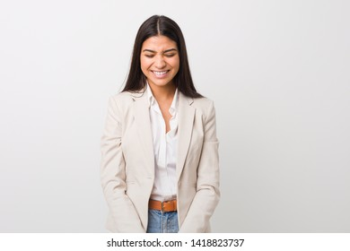 Young business arab woman isolated against a white background laughs and closes eyes, feels relaxed and happy.