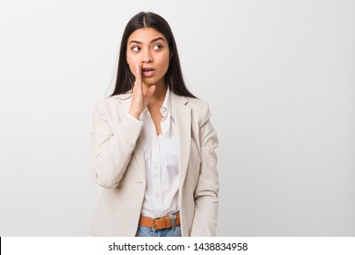 Young business arab woman isolated against a white background is saying a secret hot braking news and looking aside