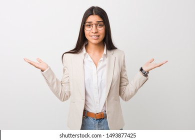 Young business arab woman isolated against a white background confused and doubtful shrugging shoulders to hold a copy space.