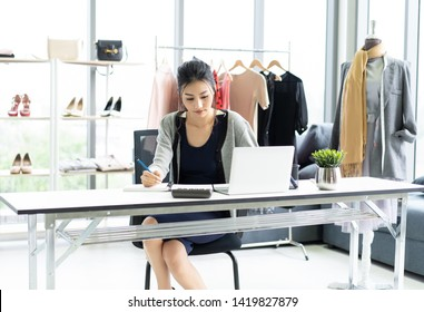 Young business Asian woman sitting at table and taking notes in notebook on table is laptop in clothes shop. Startup Small Business Owner Concept.