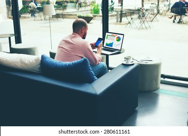 Young business busy working on laptop computer and smart phone sitting at sofa of modern coffee shop or hotel hall, entrepreneur analyzing financial information as graphics and charts on his notebook