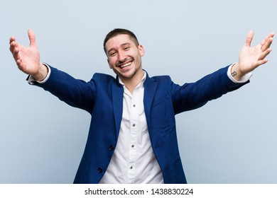 Young business caucasian man feels confident giving a hug to the camera.