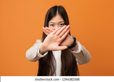 Young business chinese woman doing a denial gesture