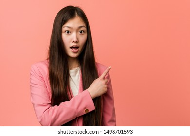 Young business chinese woman wearing pink suit pointing to the side