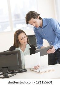 Young business colleagues discussing over digital tablet at desk in office