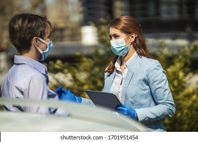 Young business colleagues with protecting masks on their faces are analyzing project outdoors and talking about it while using digital tablet.