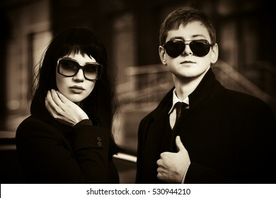 Young business couple against office building. Male and female stylish fashion model in sunglasses outdoor