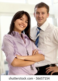 Young business couple in an office smiling