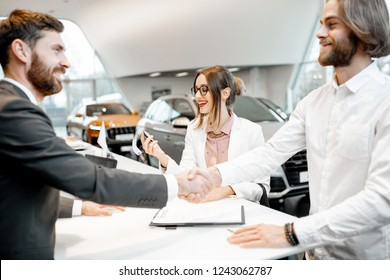 Young business couple shaking hands having a deal with salesperson at the stand buying or renting car in the showroom