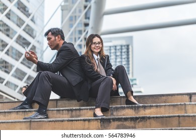 A young business couple sitting on a modern buildings environment with a smartphone.