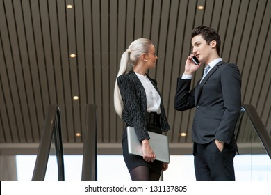 Young business couple talking on smart phone in mall.