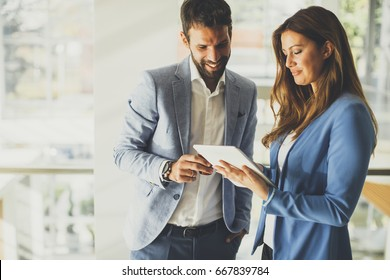 Young business couple working on tablet in modern office