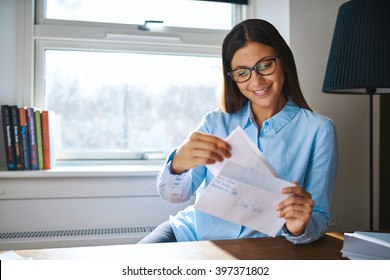 Young business entrepreneur checking her mail sitting at her desk at home with an open letter in her hand