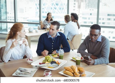 Young business entrepreneurs sitting at breakfast table in office cafeteria
