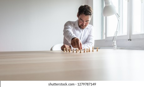 Young business executive positioning white chess pieces in a sensible structure on his office desk in a conceptual image of company structure and human resources.