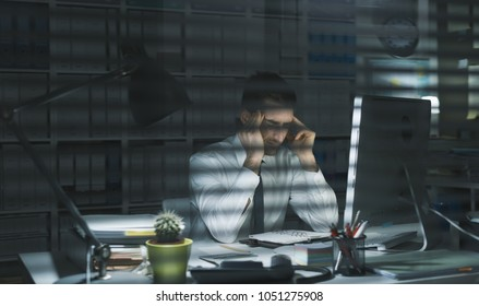 Young business executive working in the office late at night and having an headache, deadlines and stress concept