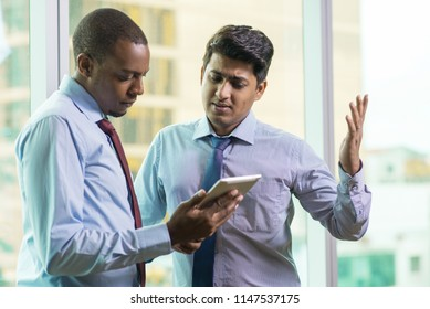 Young business executives upset with bad news. Unhappy multi-ethnic business people reviewing document on tablet computer. Bad news concept