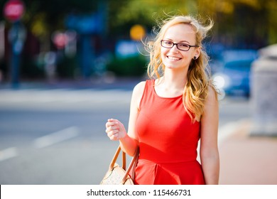 Young business girl in red dress on blurry city background