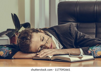 young business girl sleeping on the desk in the office. concept exhausted from work. Overworked and tired young woman sleeping on desk